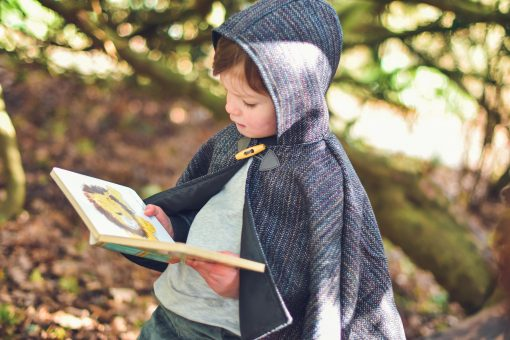 Waves and Wild Storybook Cape boy wearing grey cape reading book