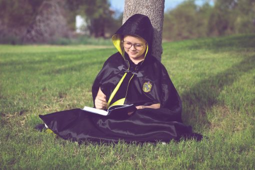 Waves and Wild Storybook Cape boy wearing Hufflepuff robe studying under a tree