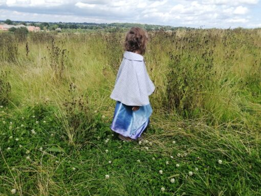 Waves and Wild Storybook Cape girl wearing grey cape from behind