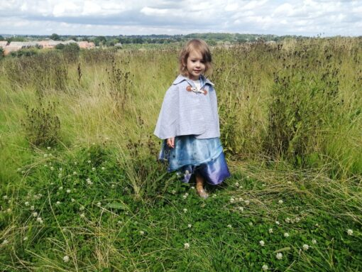 Waves and Wild Storybook Cape Girl wearing grey cape in field