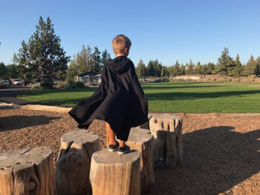 Waves and Wild Storybook Cape black from behind