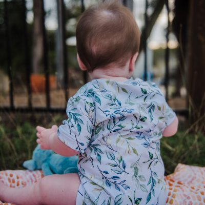 Pick and Mix bodysuit baby sat on blanket with Indigenous print